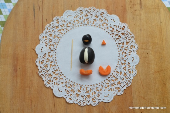 Assembling each penguin is quite simple. In this photo, observe the shape of the carrots and the placement of each component before securing with a toothpick.